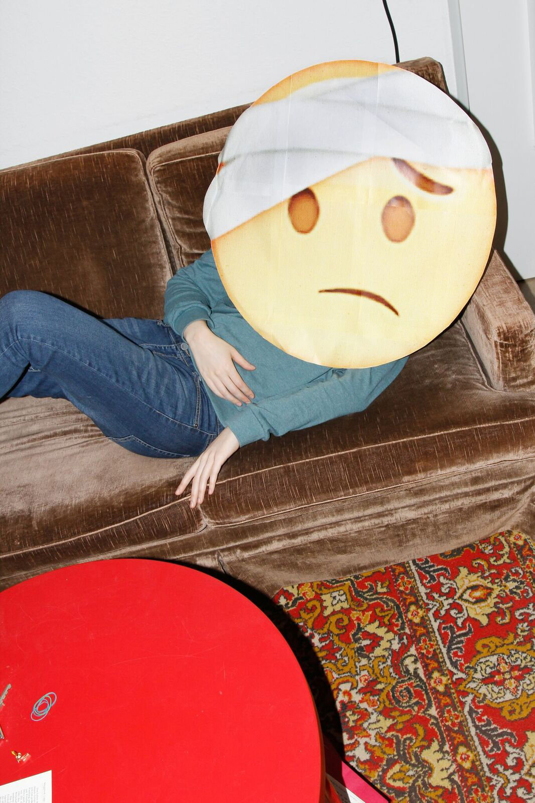 Emoji mit Kopfverband liegt auf einem Sofa (Foto: Renke Brandt)