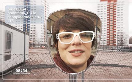Eine Frau mit Brille betrachtet sich im Spiegel - die Brille ist eine Datenbrille
