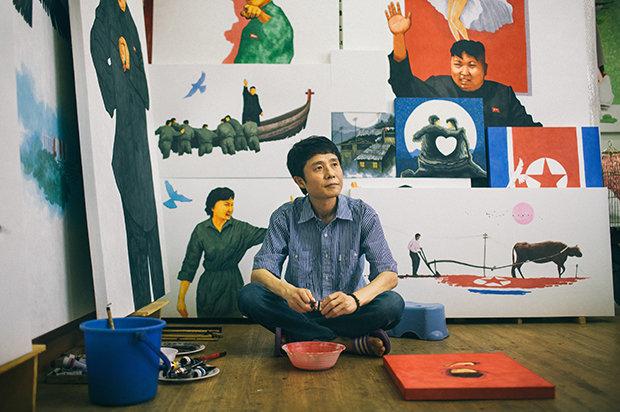 Nur auf den ersten Blick Propagandakunst: Song Byeok vor einigen seiner Werke. (Foto: Hannes Jung)