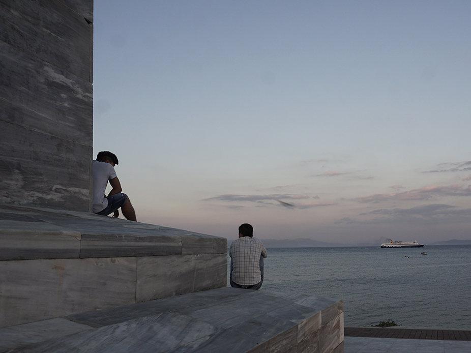 Die zwei 17-jährigen Afghanen Fadi und Saboor warten seit acht Monaten auf ihren Asylbescheid, hier sitzend auf Lesbos' Freiheitsstatue (Foto: Franziska Grillmeier)