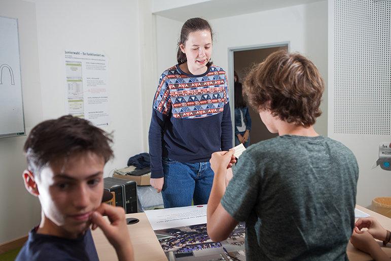 Eine Schülerin gibt ihren Wahlschlüssel bei den Schülern, die die Wahlaufsicht spielen ab und darf danach am Computer wählen