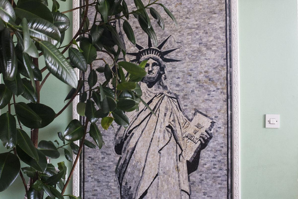 Ein Mosaik zeigt eine Freiheitsstatue auf einer grünen Wand