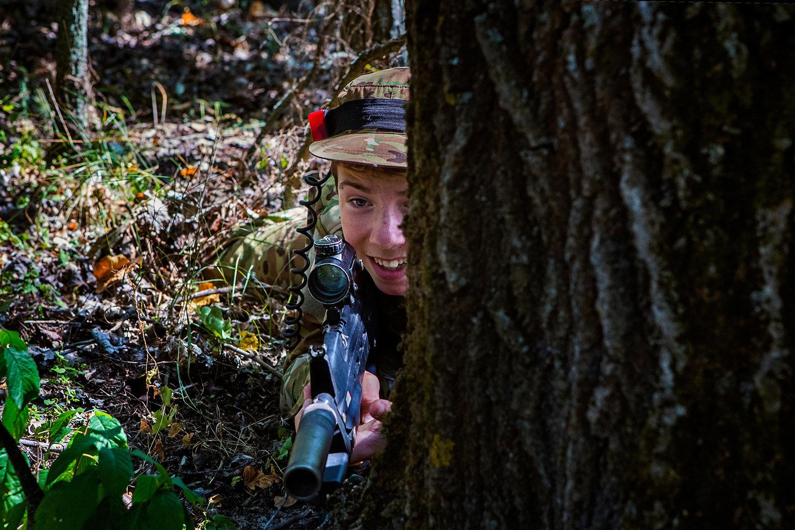 Ein Junge lauert mit einem Gewehr hinter einem Baum