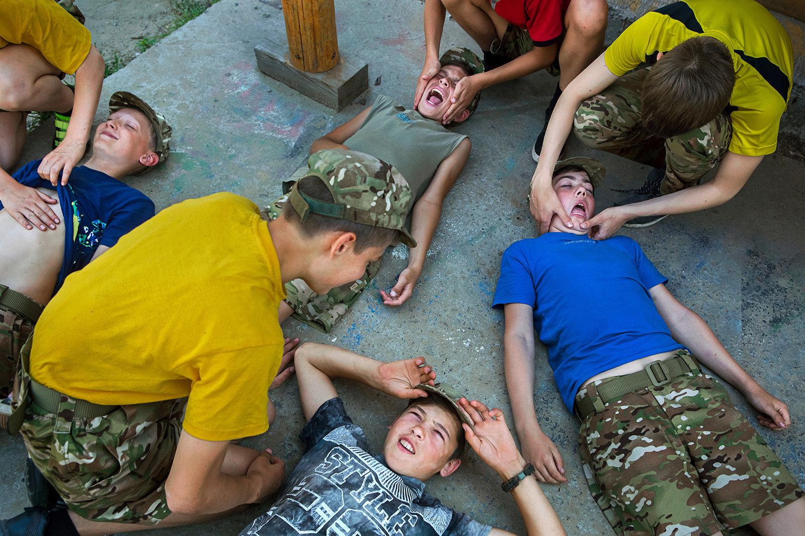 Kinder in Militärkleidung liegen auf einem Betonboden