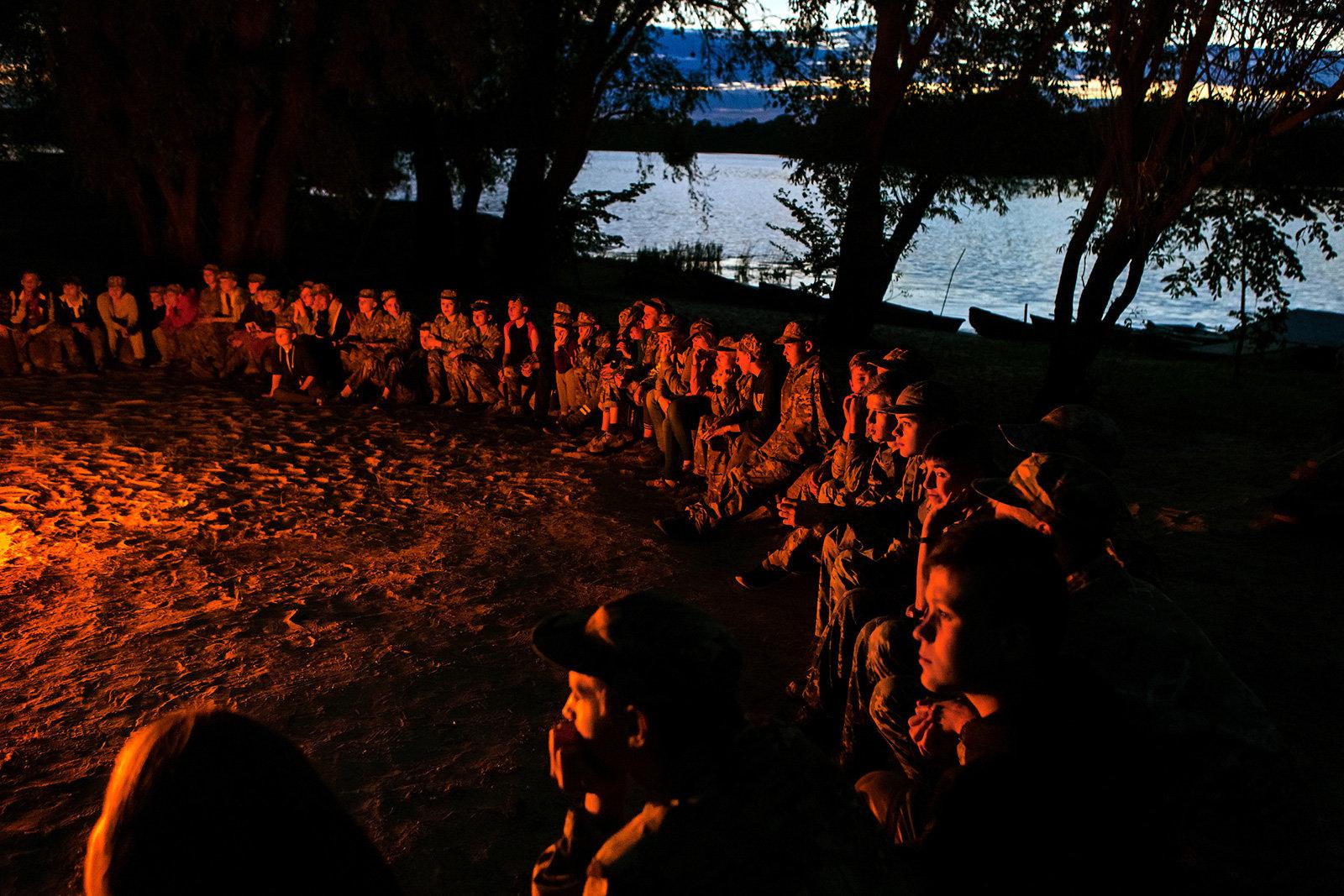 Kinder in Militärkleidung sitzen um ein Lagerfeuer