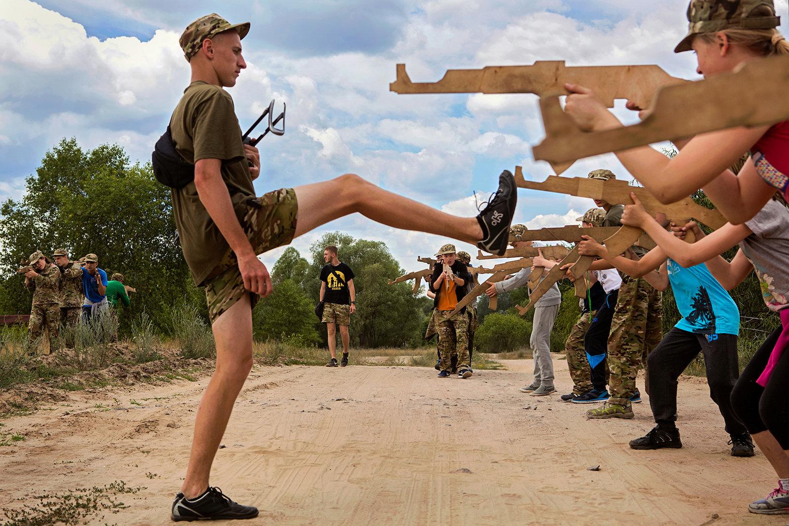 Mehrere Kinder zielen mit Holzgewehren auf einen Campleiter