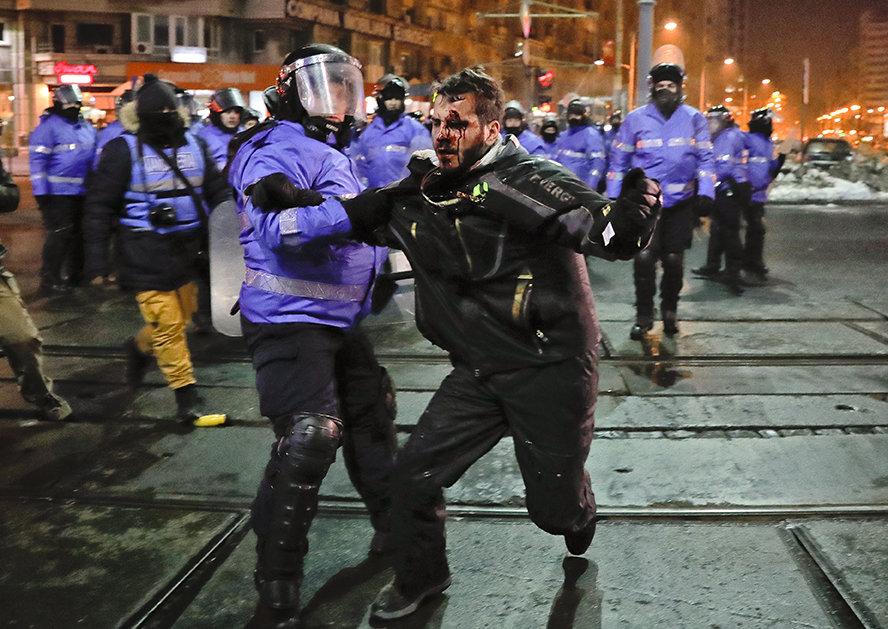 Demonstrant mit blutigen Gesicht wird von einem Polizisten festgehalten
