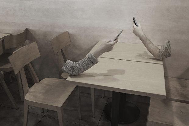 Zwei körperlose Arme, auf einen Tisch abgestützt, halten ein Smartphone in der Hand