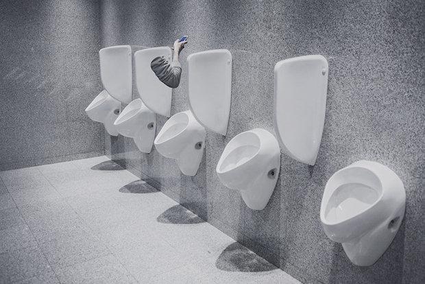 Ein körperloser Arm hält in einer Toilette ein Handy in der Hand