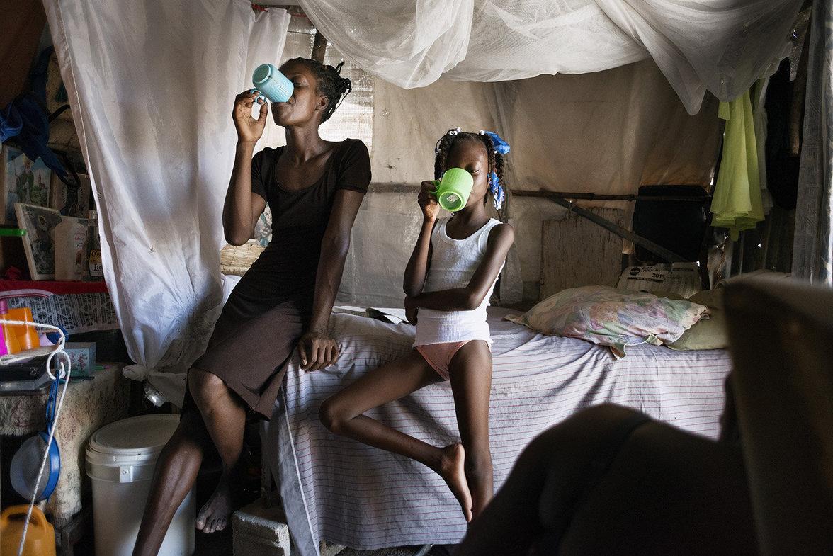 Zwei junge Frauen trinken aus Plastikbechern