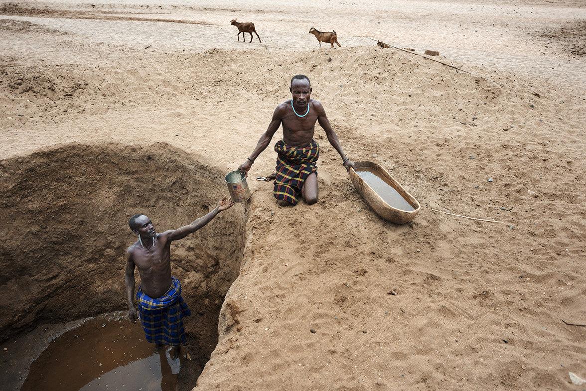 Hirten graben in einem schlammigen großen Loch nach dem Grundwasser