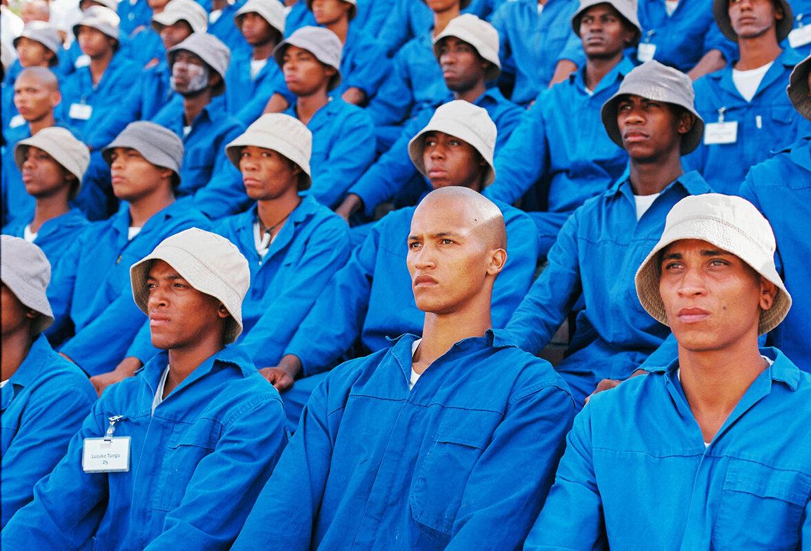 Junge Männer sitzen aufgereiht in Blaumännern.