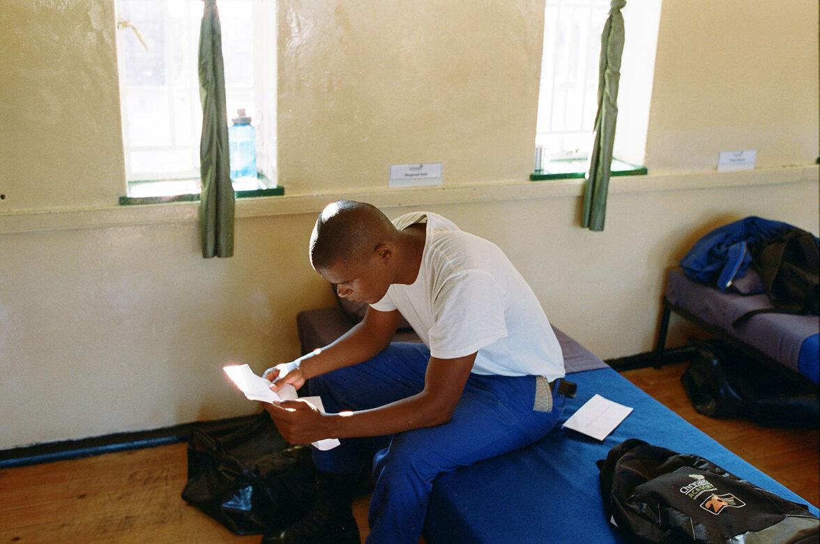 Ein junger Mann sitzt auf einem Feldbett und liest einen Brief.