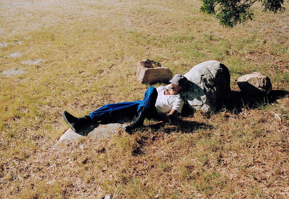 Ein junger Mann liegt mit ins Gesicht gezogenem Hut auf einer Wiese und schläft.