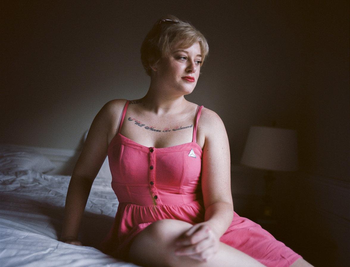 """Erika sitzt in einem rosa Kleid auf einem Bett, ihr Tattoo """"I will never be silenced"""" ist zu sehen"""