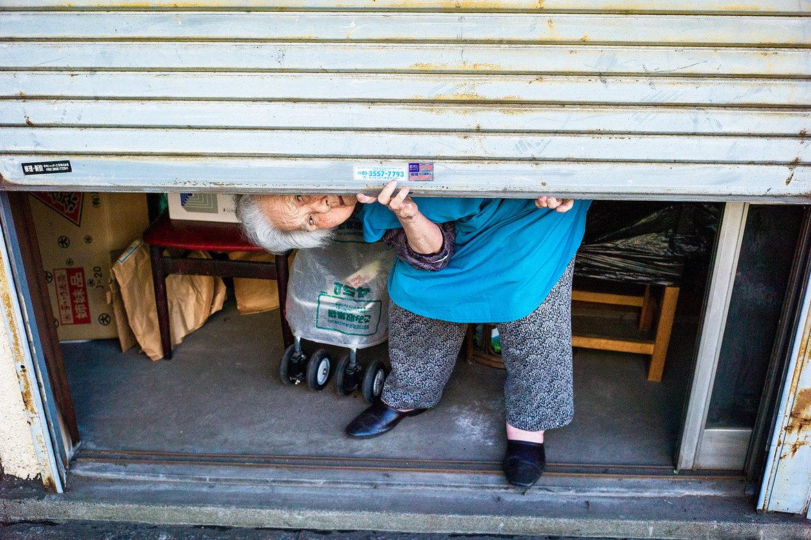 Alte Frau in einer Garage in Tokio