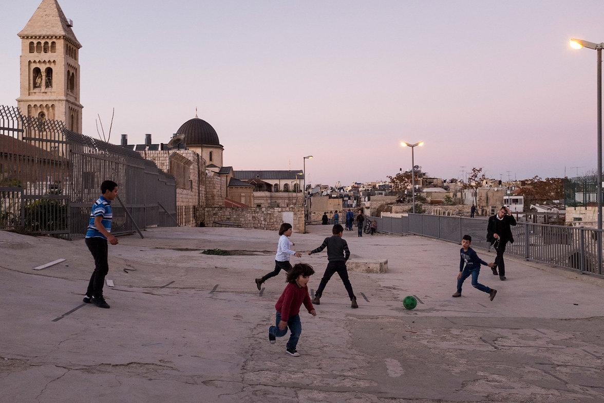 Eine Gruppe palästinensischer Kinder spielt Fußball quer über die Dächer