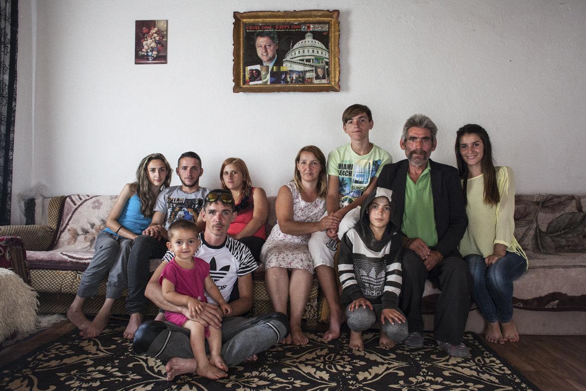 Ein Familienporträt, die Familie sitzt auf einem Sofa, im Hintergrund hängt ein Foto von Bill Clinton