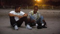"""Szene aus dem Film """"Moonlight"""": Kevin und Chiron sitzen am Strand"""