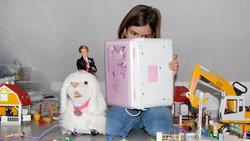 Mädchen im Kinderzimmer liest in einem Kinder-Laptop