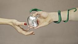Eine Hand überreicht einer anderen Hand einen Apfel, der dem Apple-Logo nachempfunden ist