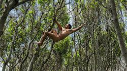 Ein nackter Mann hängt in den Bäumen
