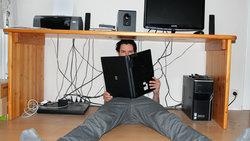 Junger Mann sitzt unter dem Schreibtisch und hält einen Laptop wie ein Buch