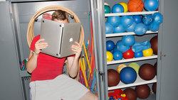 Mann in Sportkleidung hält einen Laptop, als ob er ein Buch wäre