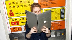 Frau im Waschsalon liest in ihrem Laptop