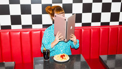Frau sitzt im American Diner und liest in einem laptop