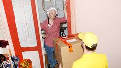 Frau mit einer Mozart-Perücke nimmt ein Paket an