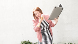Ein Mädchen ist Eis und hält dabei ein aufgeklapptes Laptop in den Händen
