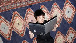 Eine Frau hält ihren Laptop wie ein Buch und liest darin