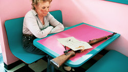 Eine Frau mit Gewehr sitzt in einem Diner