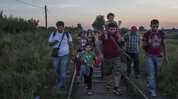 Flüchtlinge laufen Bahngleise entlang