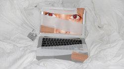 """Gesicht auf einem Laptop-Display, das mit Pflastern und Verband """"verarztet"""" wurde"""