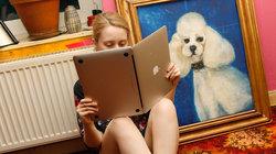 Junge Frau hält einen Laptop wie ein Buch, als würde sie darin lesen