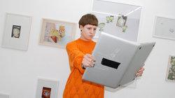 Eine Frau hält einen Laptop wie ein Buch
