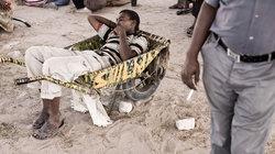 Ein Somaliländer liegt in einer Schubkarre und kaut Khat