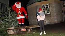 Eine Frau steht neben einem Weihnachtsbaum und einer Nikolaus-Figur und liest in ihrem Laptop
