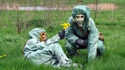 Zwei Menschen in Sicherheitskleidung und Gasmasken liegen auf einer Wiese