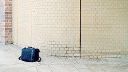 Herrenlose Reisetasche vor Ziegelwand; Foto: Johannes Heinke