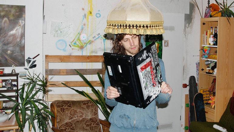 Mann steht unter Lampenschirm und liest in Laptop