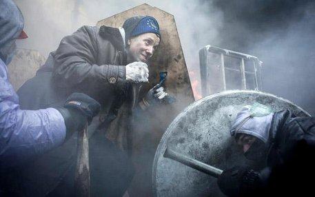 Auf dem Maidan in Kiew schützen sich Demonstranten mit selbst gebastelten Schildern gegen das hochgerüstete Militär