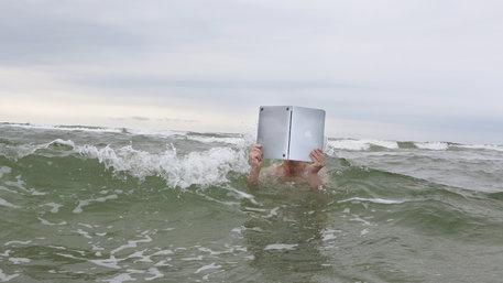 Jemand schwimmt im Meer und liest dabei in einem Laptop wie in einem Buch
