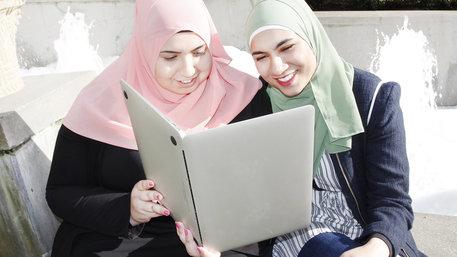 Zwei junge Frauen mit Kopftuch schauen auf einen Laptop, als wäre es ein Buch