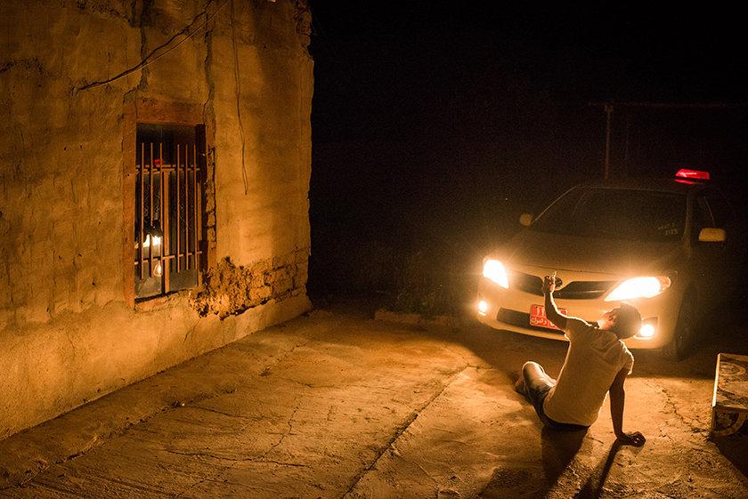 Im Scheinwerferlicht eines Autos sitzt ein junger Mann telefonierend am Boden  (Foto: Chris Grodotzki)